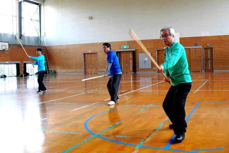 棍術を練習する男性会員達の写真