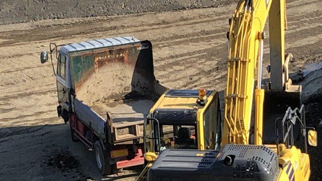 シャベルカーがトラックの荷台へ、車体を旋回させて、土を運ぶ写真