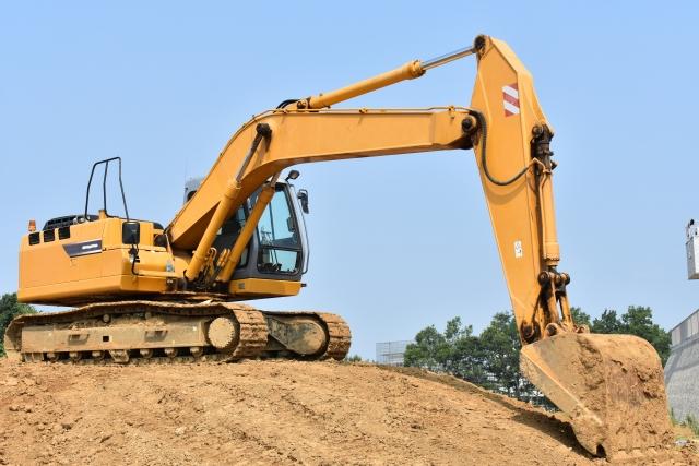 シャベルカーがアームを伸ばし、つ土を掘る写真