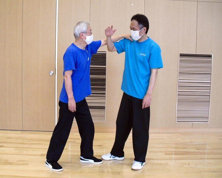 陳式太極拳 懶扎衣の用法例、相手が右肩を押さえてきたのを右手のポン勢で接触した写真