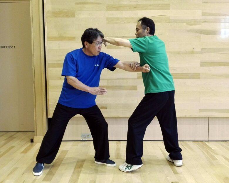 単鞭の打法の用法例2 相手の左手を引っ掛けながら、左単鞭を打っている写真