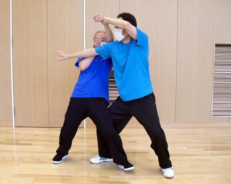 陳式太極拳 懶扎衣の用法例、チー勢から下方への按勢に換勁し、相手を後方へと倒している写真