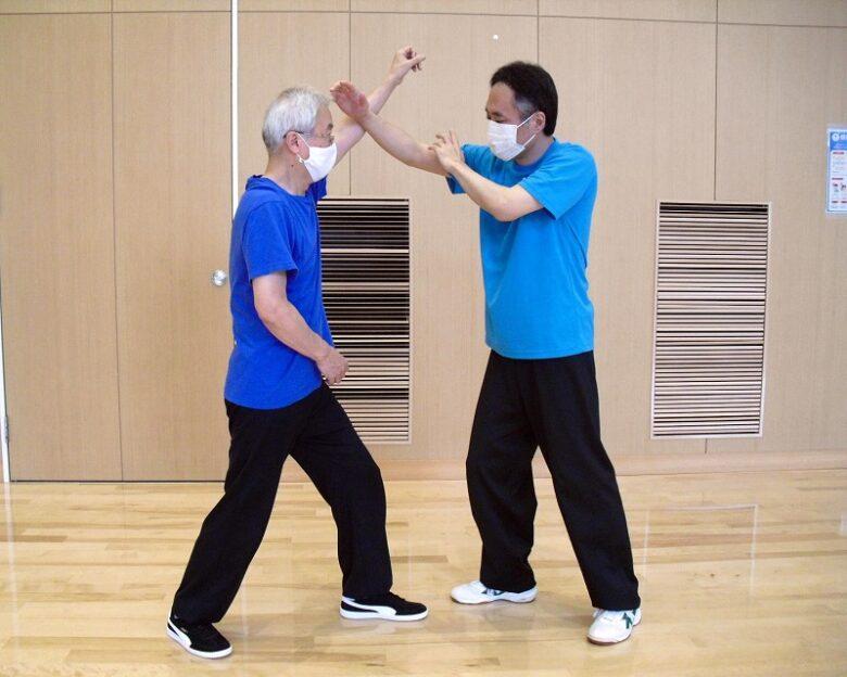 陳式太極拳 懶扎衣の用法例、相手が右肩を押さえてきたのを右手のポン勢ではね上げている写真