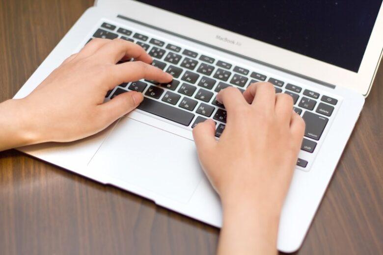 パソコンのキーボードを打つ人間の手の写真